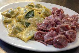 Teigtäschchen aus rosa Nudelteig, gefüllt mit geräuchertem Scamorza-Käse und Radicchio, mit knusprigem Speck serviert